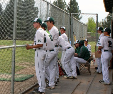 The baseball team watches in suspense in the cage. (Photo by Makayla Smith)