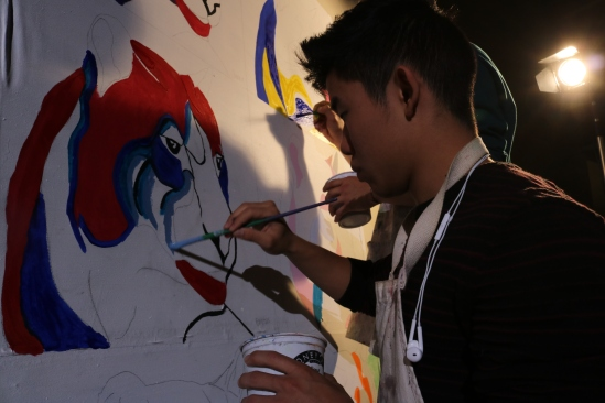 Senior Cody Kurahara paints during the assembly that took place during 3rd and 4th period. (Photo by Alex Ng)