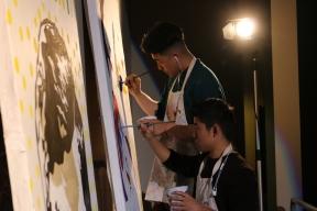 Senior Sage Yang (top) and Cody Kurahara (bottom) work together to finish the painting.