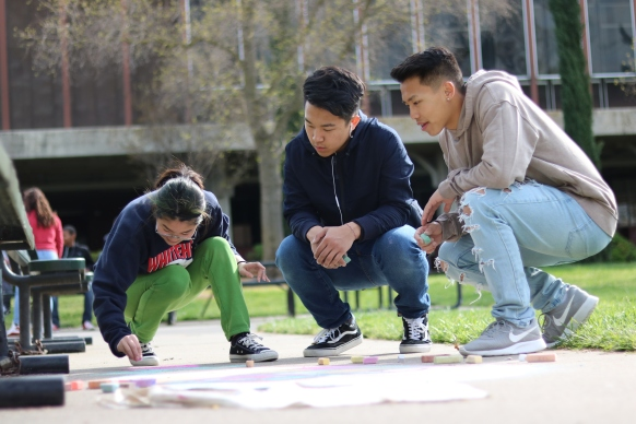 Kennedy students Jessica Fong (left), Sage Yang (middle), and Einston Vue (right) create chalk art on the sidewalk in the quad. (Photo by Alex Ng)