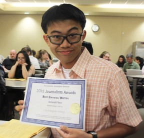 Clarion Chief Editor Christopher Wong poses proudly in classroom with one of his numerous awards from the May 8 event. Photo by Jazmin Flemmer