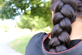 Capturing her classmates' antics, Aryanna Zavala-Cortez (12) faces forward with her hair in a braid placed under her camera strap. After a summer of leisure, she practiced her photography with returning comfort. (Photo by Cynthia Dominguez)