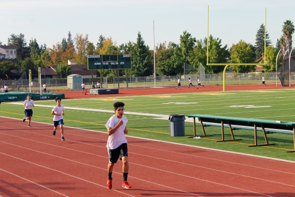 Physical education students run around the track during first period. Runners of different speeds were dispersed between the foreground and background. (Photo by Enia Chanthapaseuth)