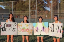 (From L to R) Jessie Guan (12), Sarah Wong (12), Angela Hu (12), and Jan Li (12) hold the posters the lowerclassmen made for them for senior night. (Photo by Bruce Tran)
