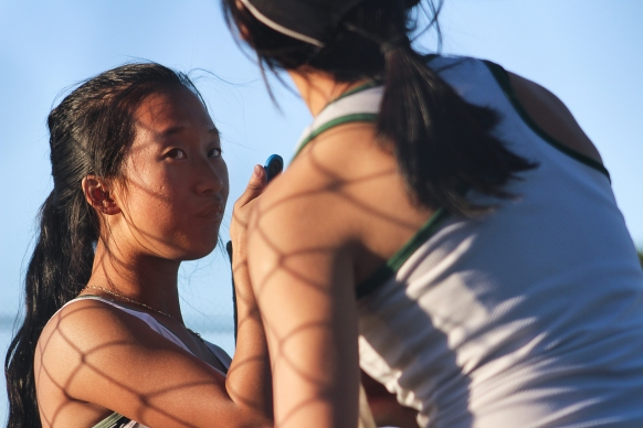 (From L to R) Payia Moua (12) and Angela Hu (12) rehydrate themselves before the game begins again. (Photo by Bruce Tran)