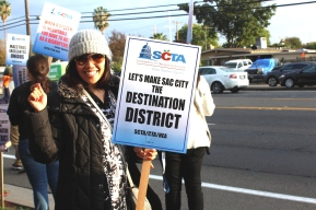 After noticing a Clarion photographer, JFK office technician Estela Brown displays her sign to show her commitment to making SCUSD an appealing district for teachers. (Photo by Chris Wong)