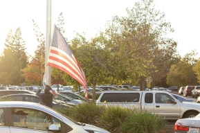 With the sound of horns honking from supporters driving by and cars silent as their loud drivers rally at the sidewalk, a man removes the flags from the pole outside the Serna Center for the day. (Photo by Chris Wong)