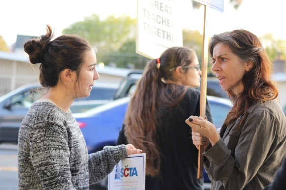 Amidst the roar of the teachers' rally, Kennedy senior Danke Stroup (left) and Kennedy math teacher Martha Sault (right) meet for the first time. (Photo by Chris Wong)