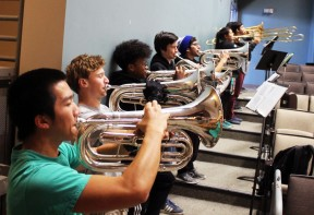 Kennedy low brass players are lined up along the wall in the auditorium for the event. Photo by Clarion staff