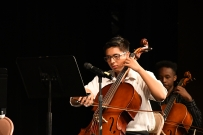 Focusing intently on his music, cellist Ethan Pham-Aguilar (10) plays for the orchestra's first performance of the year. This is Pham-Aguilar's first year in the Kennedy orchestra. (Photo by Sarif Morningstar)