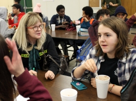 Enjoying her cocoa, freshman Emma Williams discusses the meaning of a book with her english teacher, Mary-Jo Banieki.