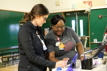 Setting up their stations, Nurses consult teach other while accessing a data-collecting program.
