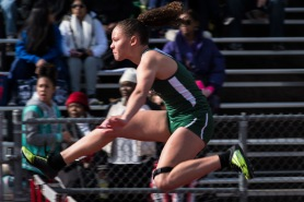 Karissa Jones strategically hurdles to the finish line on the varsity women's 100m shuttle hurdle event. Photo by Sarif Morningstar