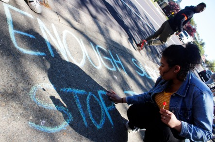 "Artistic students cover the ground with chalk all around the front of the school. Jessica Nunez (11) writes ""enough silence stop gun violence"""