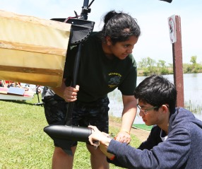 Mia Whitfield helps Michael Huang with boat repeller adjustments between races.
